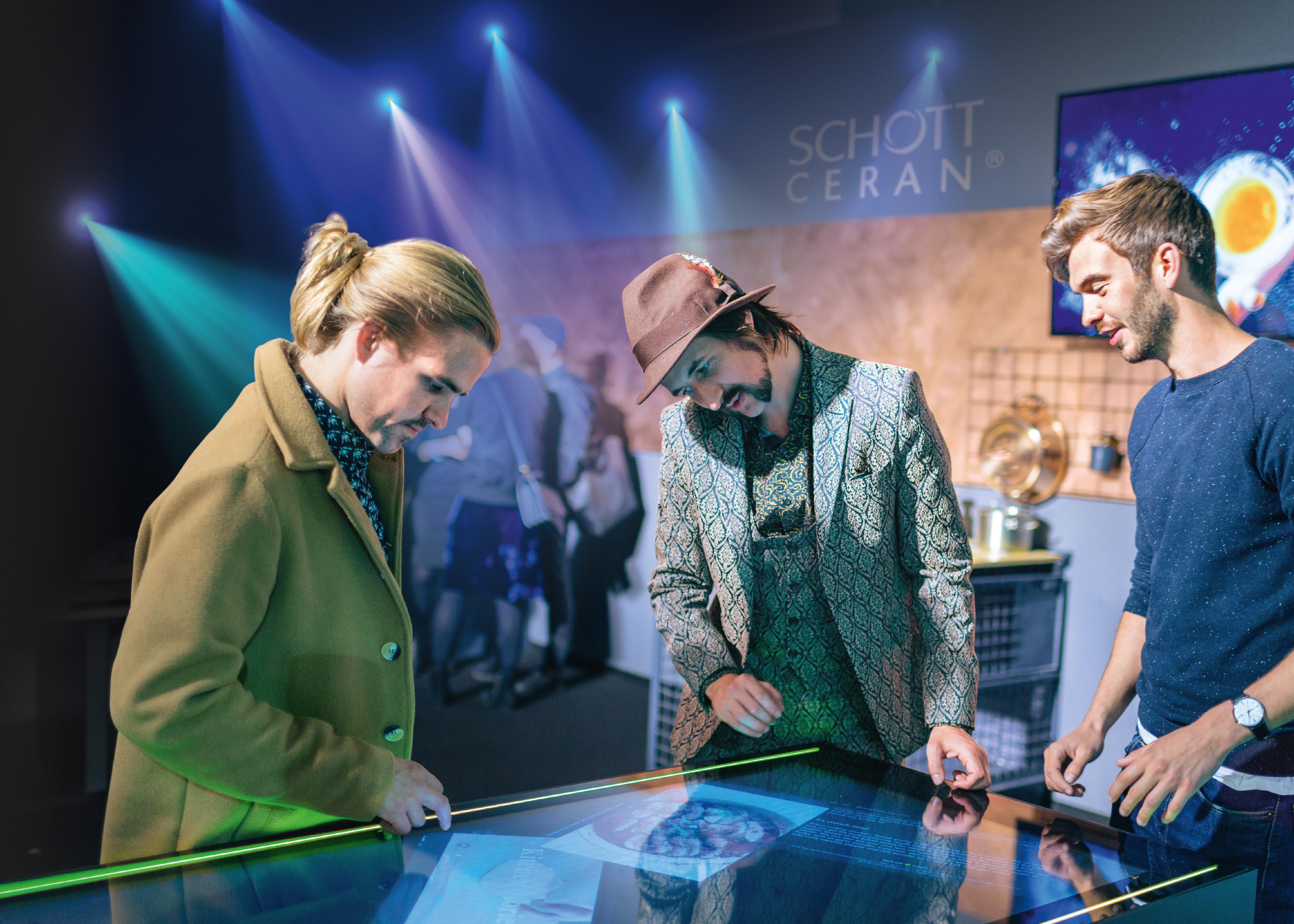 Eine Gruppe junger Leute betrachtet eine SCHOTT CERAN EXCITE® Glaskeramik-Kochfläche auf einer Ausstellung Zwei SCHOTT Qualitätsingenieure prüfen eine SCHOTT CERAN® Glaskeramik-Kochfläche