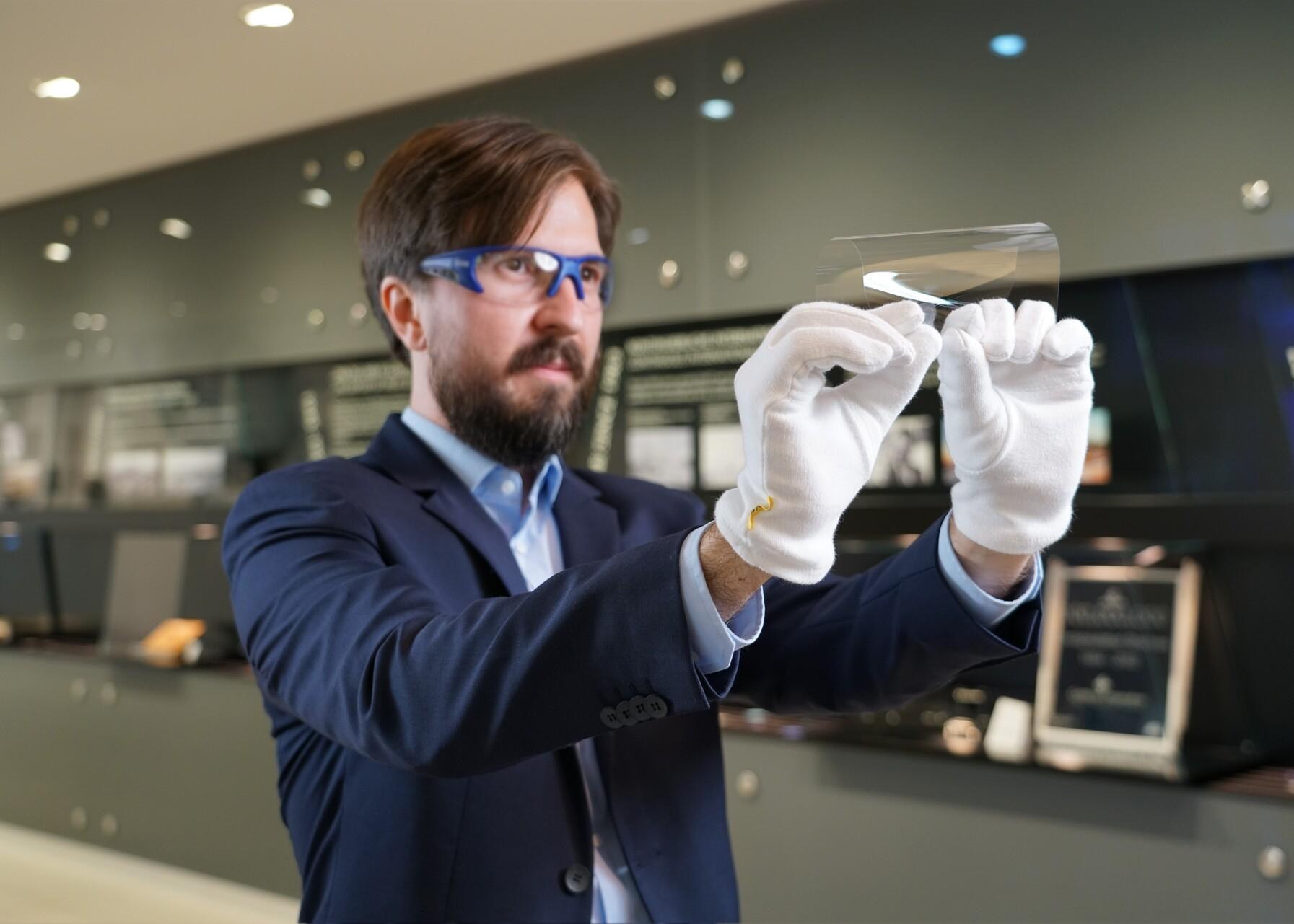 Mann im blauen Anzug demonstriert die Flexibilität von SCHOTTs ultradünnem Deckglas für Smartphones