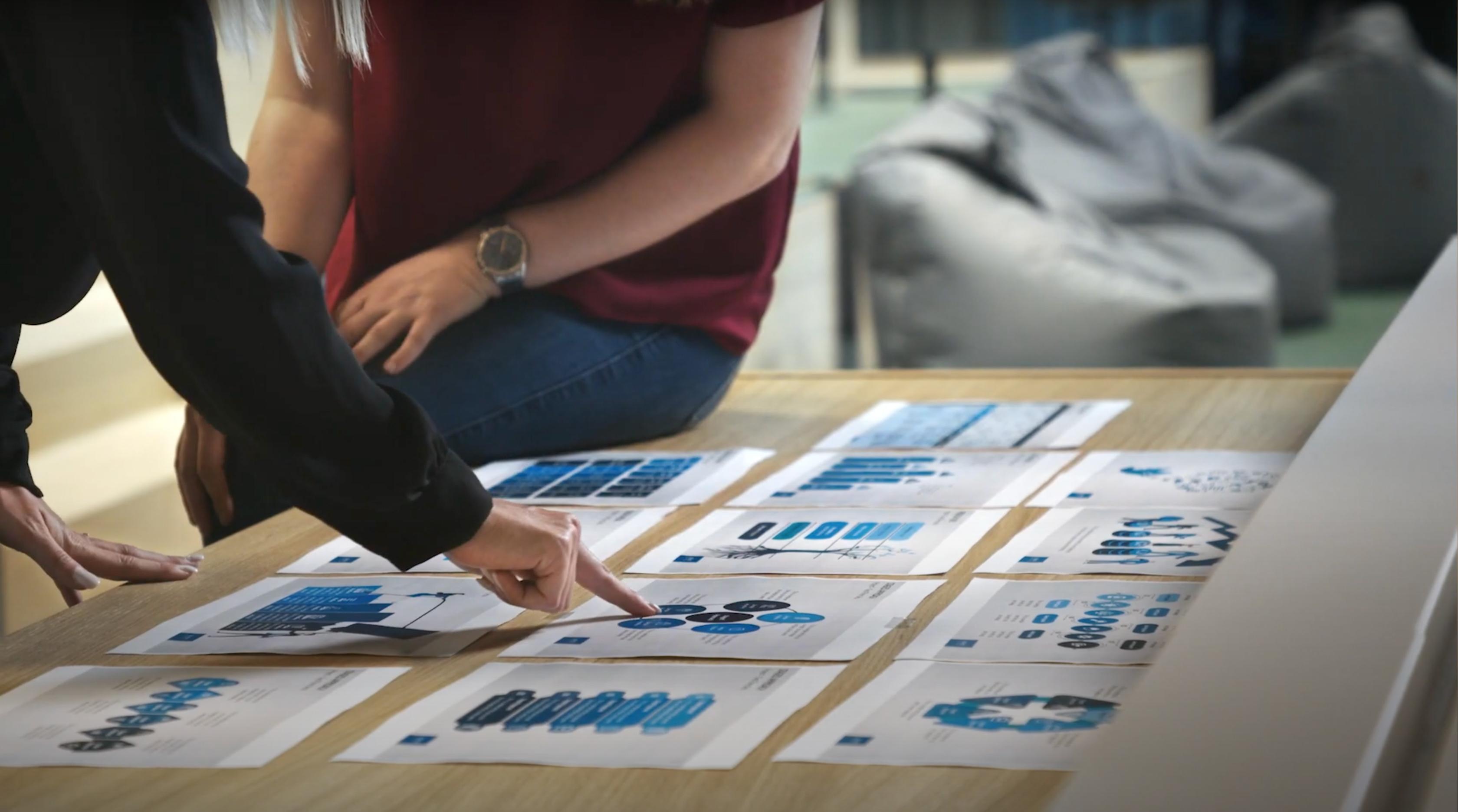 Junge Leute, die auf einen Satz Karten auf einem Tisch zeigen