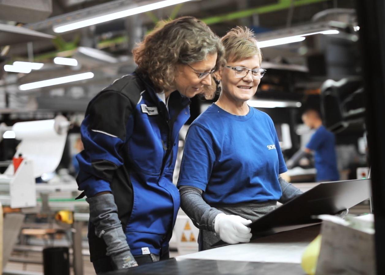 Zwei SCHOTT Qualitätsingenieure prüfen eine SCHOTT CERAN® Glaskeramik-Kochfläche